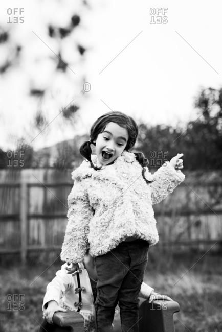 Black and white portrait of girl standing atop an outdoor toy