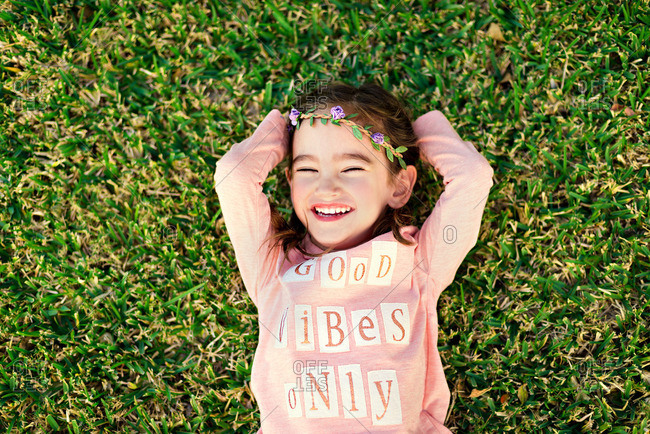 Little girl lying in the grass wearing a flower crown