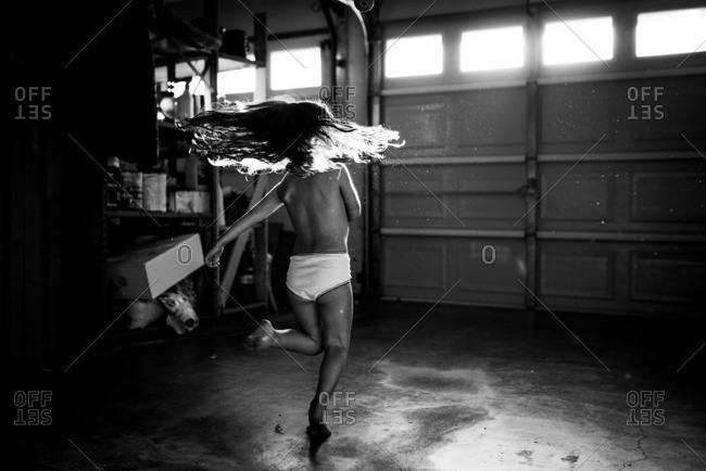 Girl twirling in a garage wearing underpants