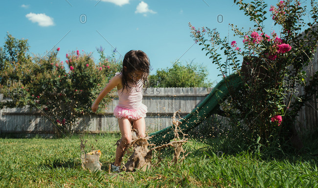 Little girl wearing pink tutu jumping in a mud puddle