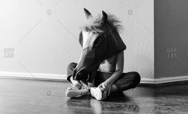 Child wearing a horse head mask