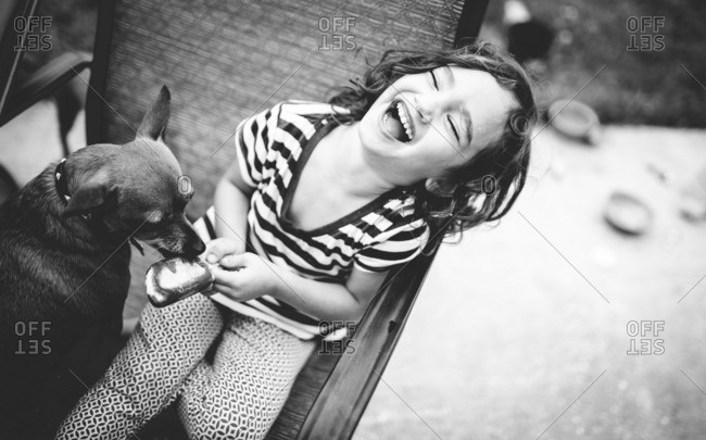 Little girl laughing while dog licks her ice cream treat