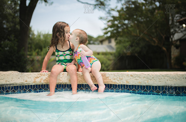 Little girls sitting by a pool kissing