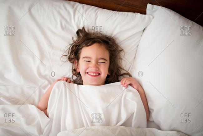 Little girl lying in bed smile