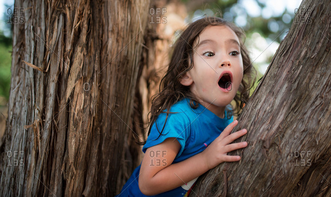 Young girl climbing a tree with a surprised expression