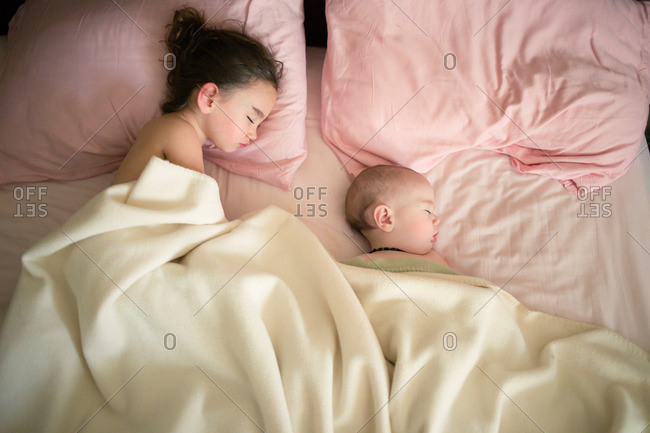 Two little girls sleeping in a bed with pink sheets