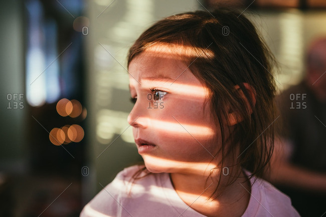 Sad little girl with lines from window light on her face