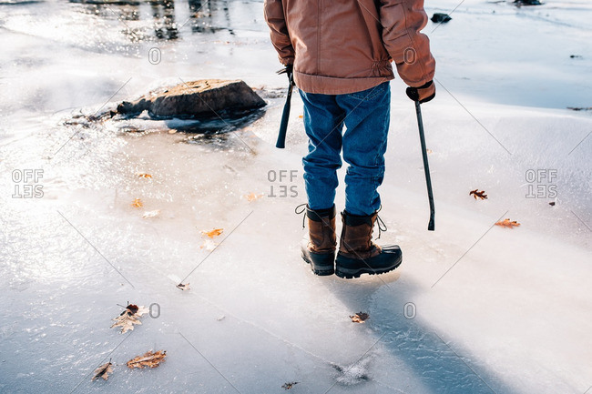 Man standing on an icy lake with tools