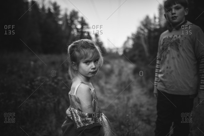 Little girl standing by her brother outdoors with a mad look on her face