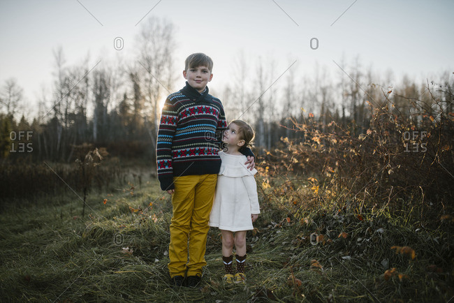 Siblings standing in a rural field with their arms around each other