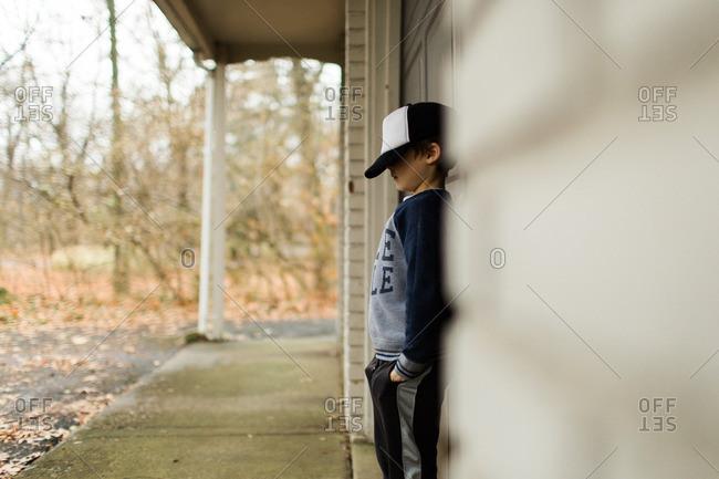 Boy standing outside on porch wearing baseball cap