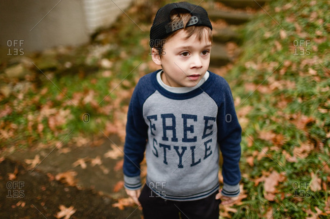 Portrait of a little boy standing outside wearing sweatshirt and baseball cap