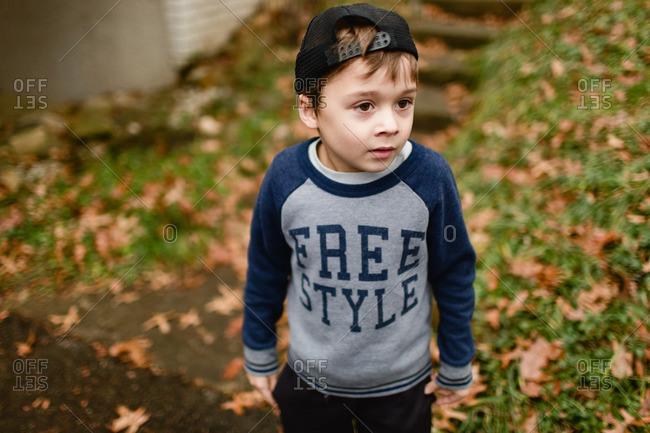 Portrait of a little boy standing outside wearing sweatshirt and baseball cap
