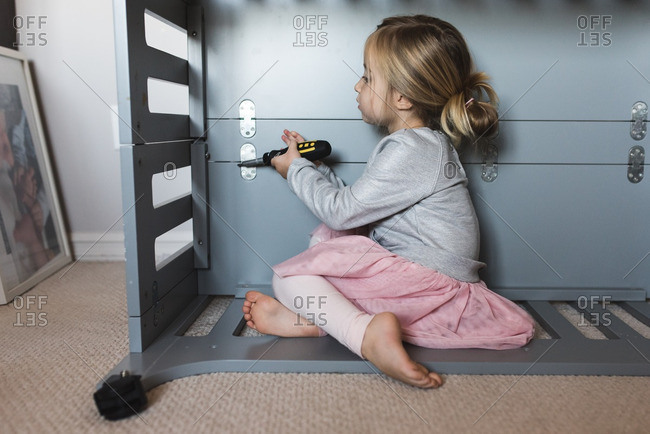 Little girl using screwdriver on a piece of furniture