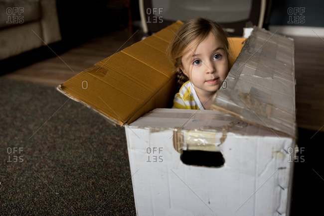 Little girl playing in a large box