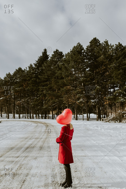 Woman standing on a wintery road with a red heart balloon