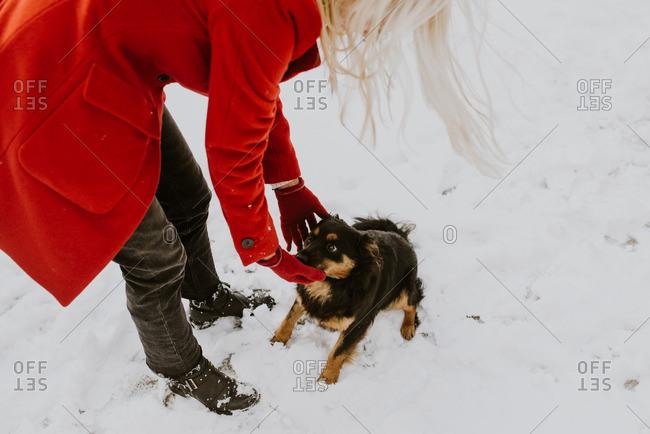 Woman wearing red coat reaching down to pet a dog