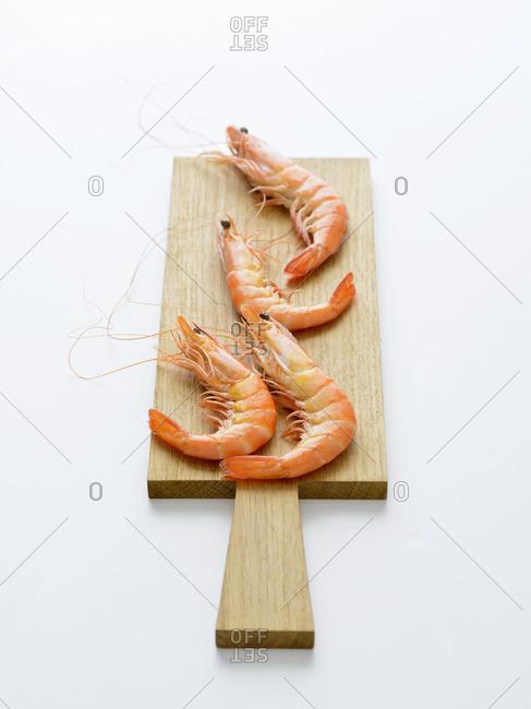 Four whole prawns on a cutting board
