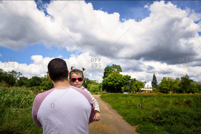 A little girl in sunglasses is carried through fields by her father