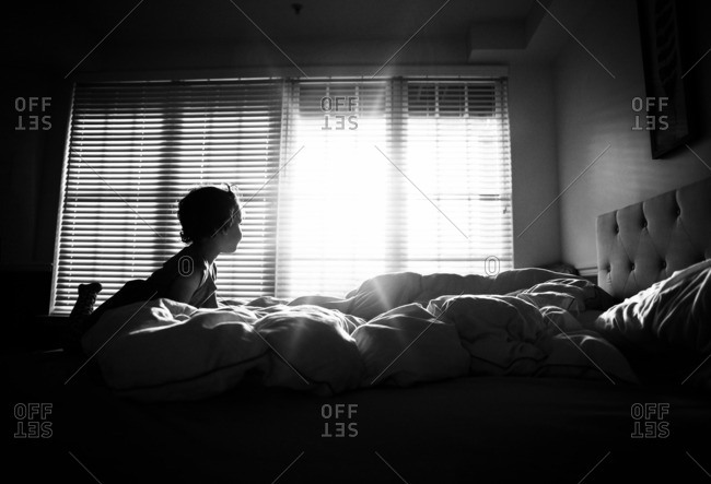 A little girl looking out a bedroom window with a sun streaming in