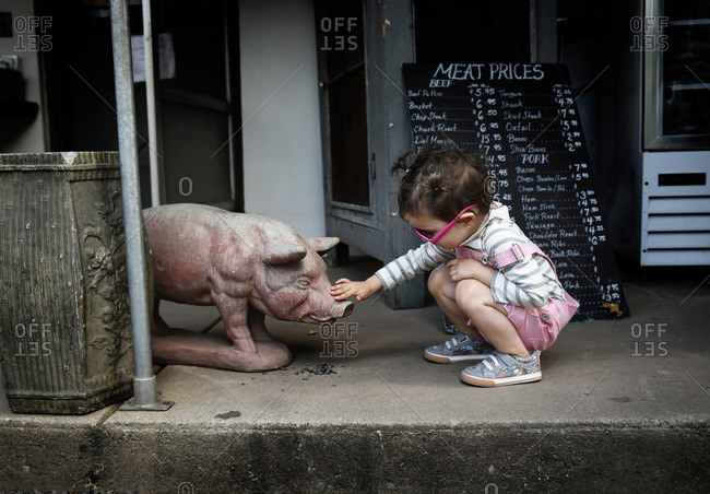 A little girl pets a pig statue at a farm
