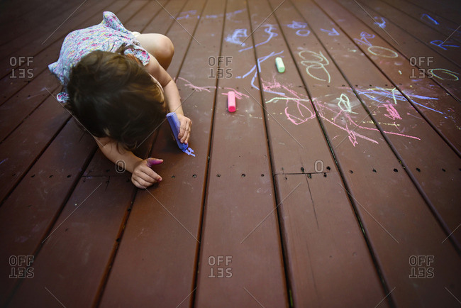 A little girl coloring with chalk on a deck in the summer