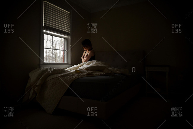 A woman surrounded by shadow sits in bed and looks out a window