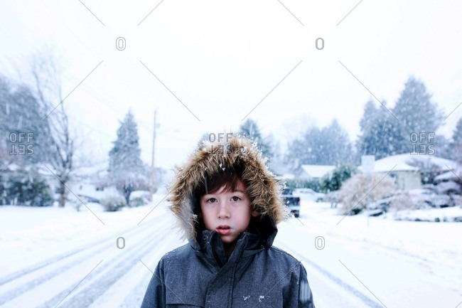 Boy standing outside on a snowy road