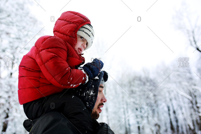 Little boy riding on father's shoulders on a snowy day