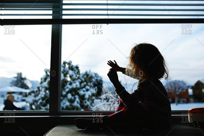 Silhouette of child waving to someone outside from a window on a snow day