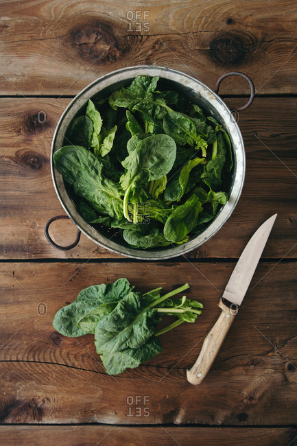 Spinach leaves in a metal colander with knife on a wood table