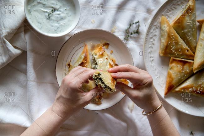 Eating Greek spanakopita with Tzatziki dip