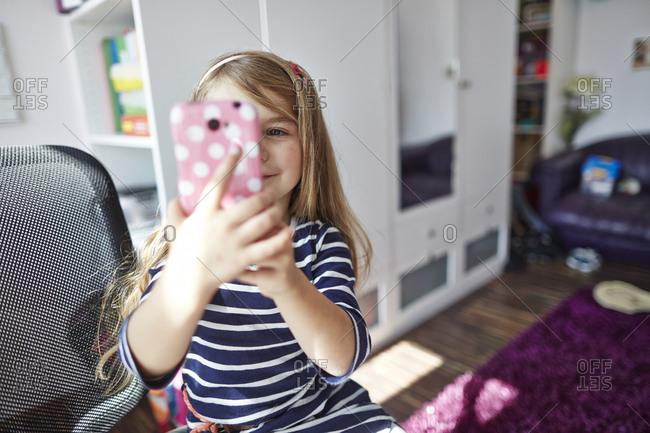 Smiling girl holding cell phone