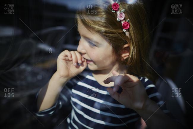 Girl behind windowpane