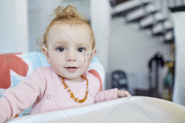 Portrait of baby girl in highchair