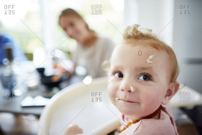 Baby girl with food remains in her face and mother in background