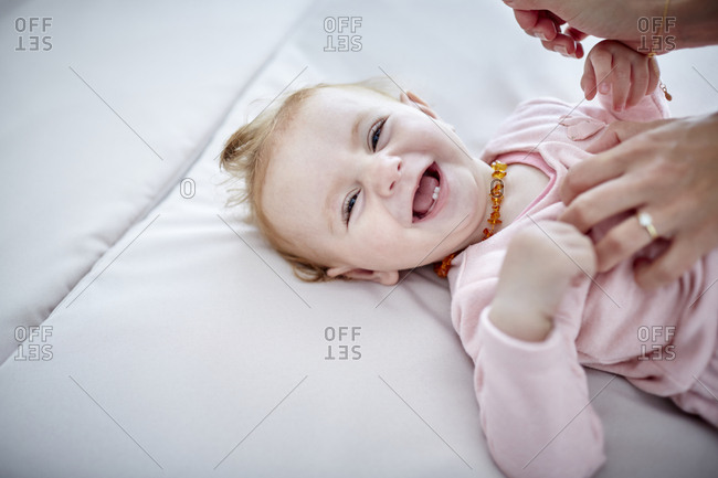 Mother tickling happy baby girl