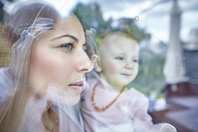 Mother and baby girl looking out of window