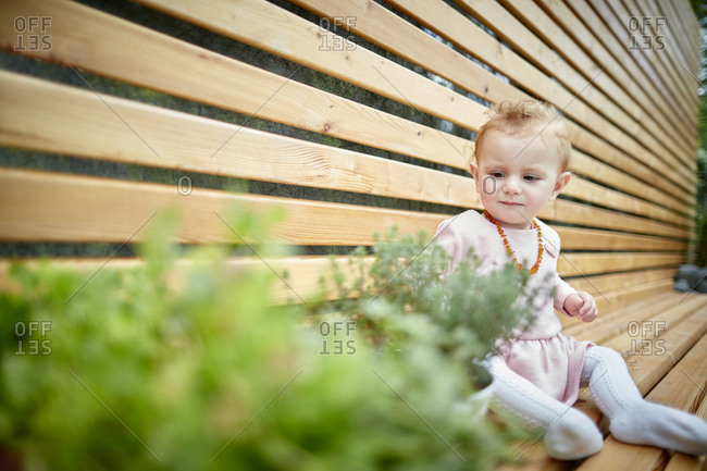 Baby girl sitting on bench next to potted plants