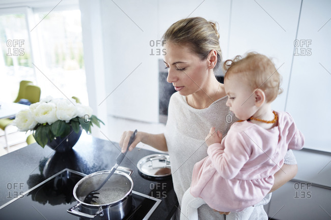 Mother with baby girl cooking