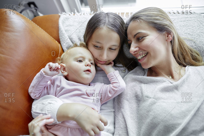 Mother with daughter and baby girl relaxing at home