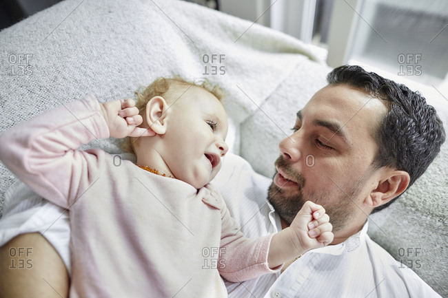 Father and baby girl lying at home