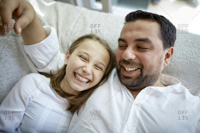 Happy father and daughter lying at home
