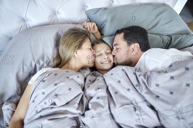 Parents kissing daughter in bed