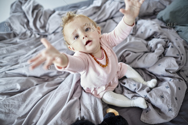 Baby girl in bedroom reaching out her arms
