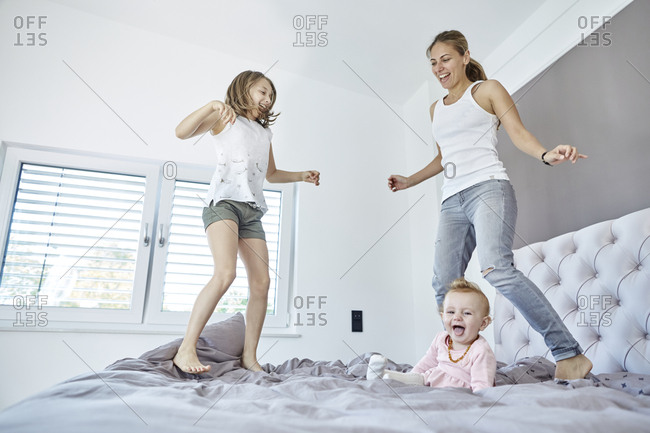 Mother with daughter and baby girl jumping on bed
