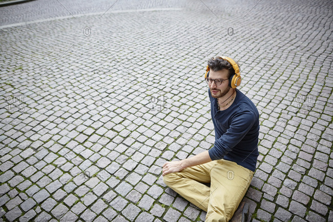 Young man sitting on a square listening to music