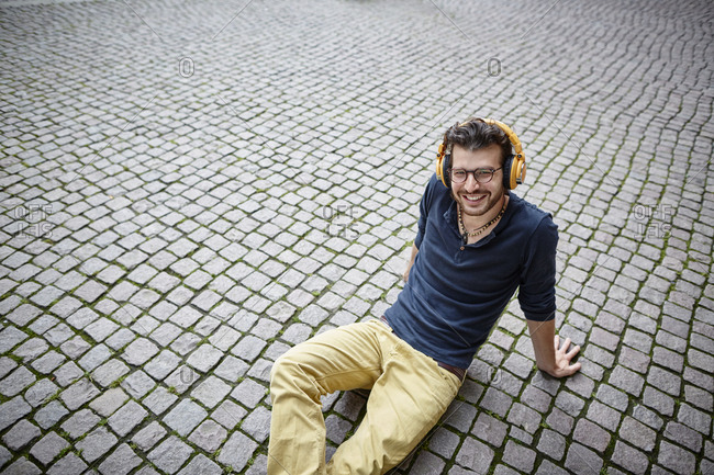 Smiling young man sitting on a square listening to music