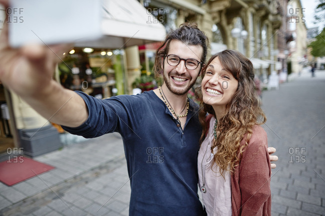 Smiling young couple taking a selfie in the city