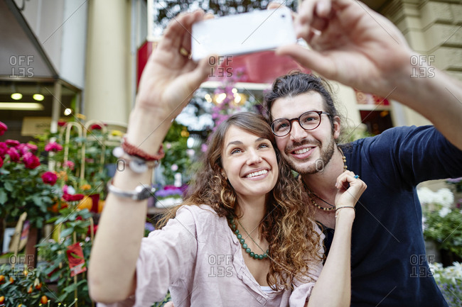 Smiling young couple taking a selfie in front of a flower shop